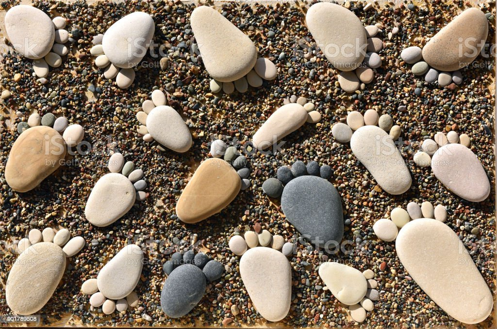 Pebble stones arranged like footprints on the beach stock photo