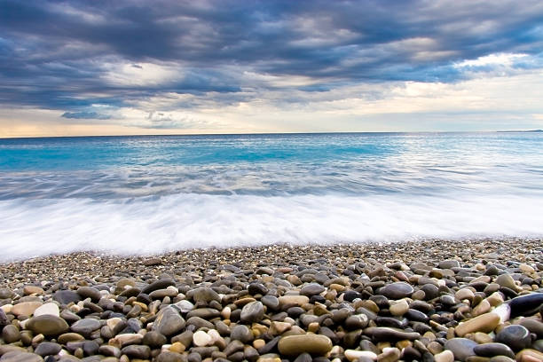 Pebbled beach and a bright blue sea stock photo