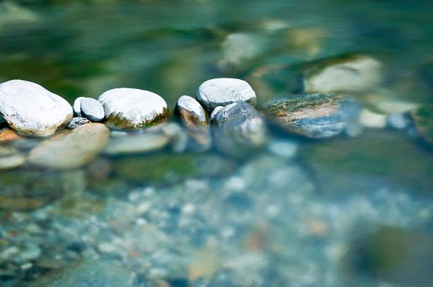 cailloux et les pierres de rivière l'eau à disposition - source naturelle photos et images de collection
