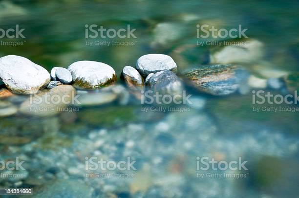 Photo of Pebbles and arranged stones in river water