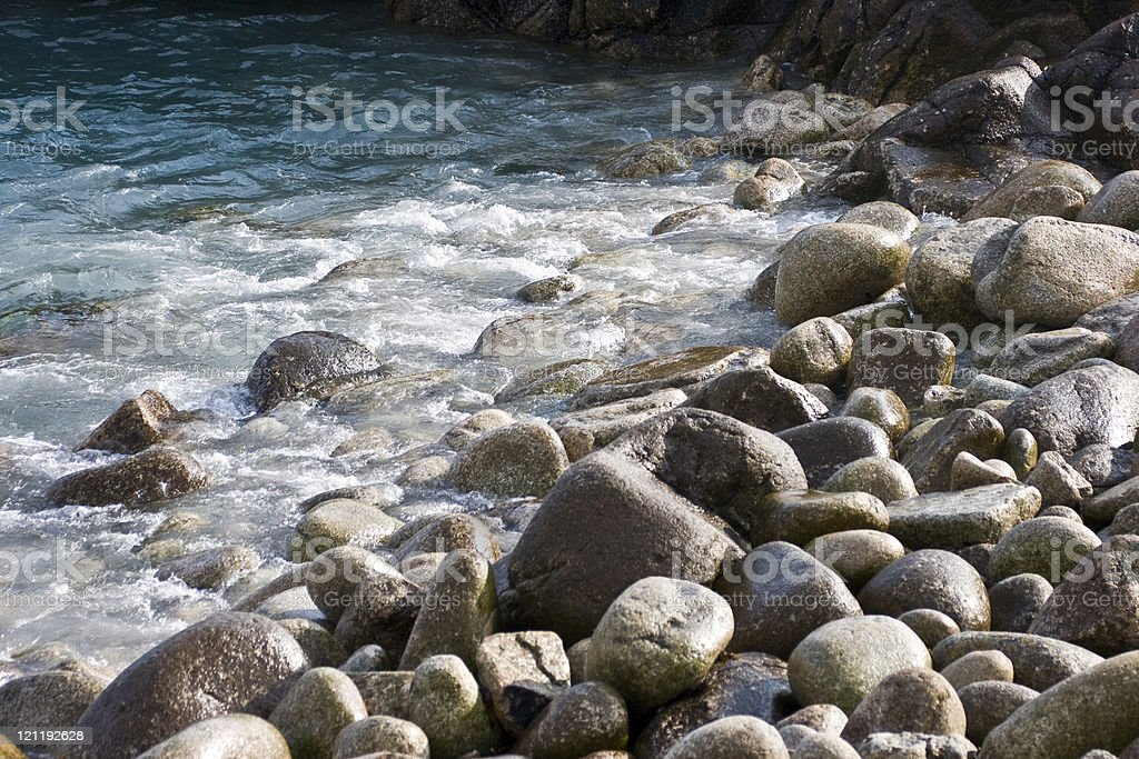 Pebbles and rocks with sparkling blue sea royalty-free stock photo