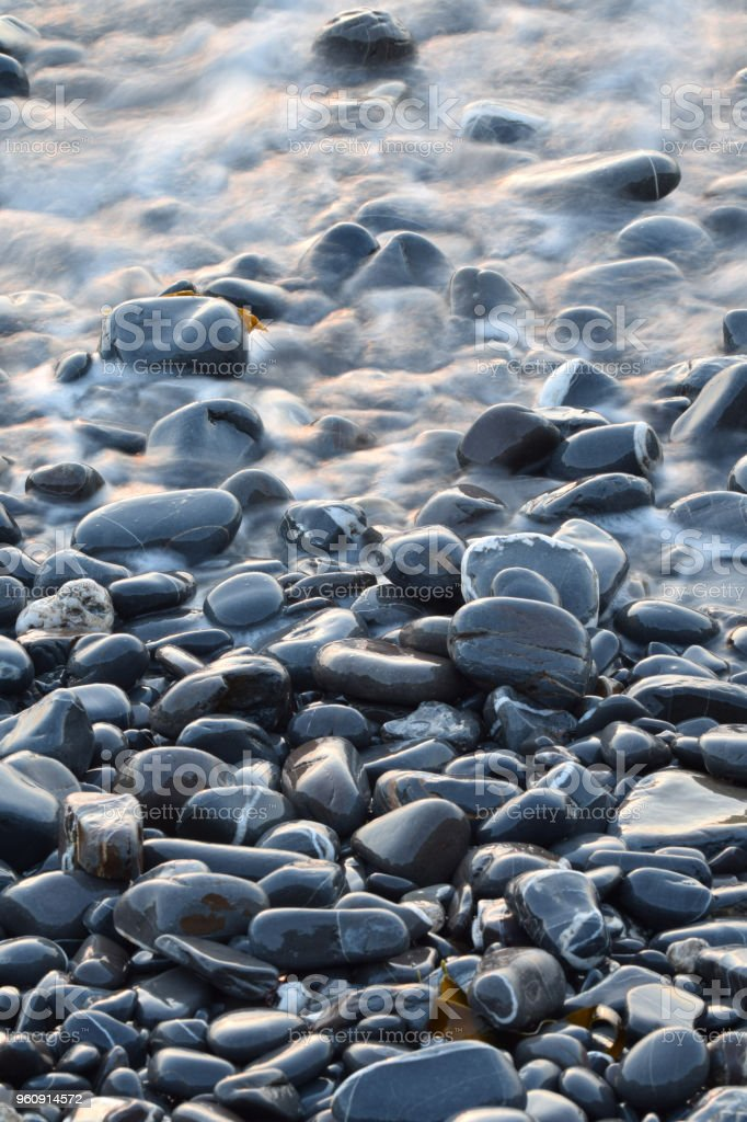 Pebbles in a retreating wave stock photo