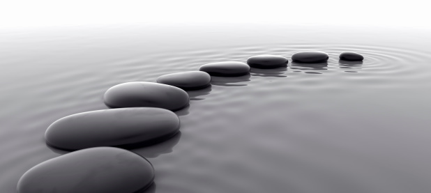 Studio-like royalty free 3d rendering of a row of shiny black pebbles.