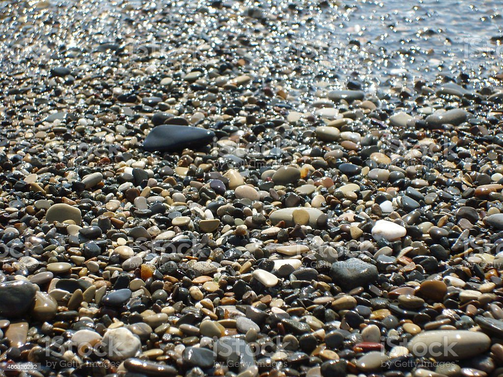 Pebbles on the beach with sea wave stock photo