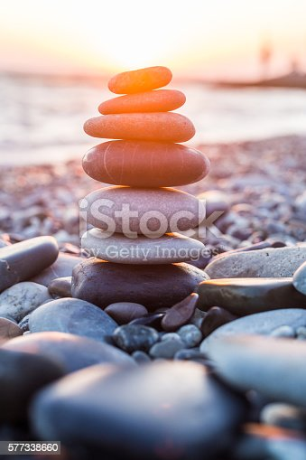 istock Pebbles pyramid on beach in sunset time 577338660