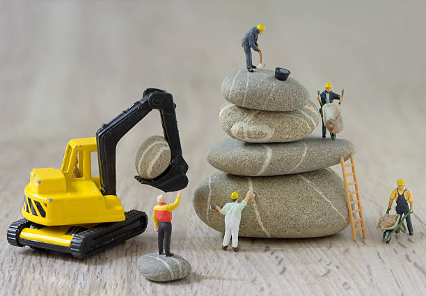 pebbles stack and figurines workers - figurine stock photos and pictures
