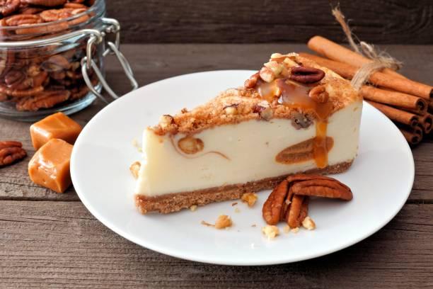 pekannuss-karamell-käsekuchen mit holz hintergrund - zimt pekannüsse stock-fotos und bilder