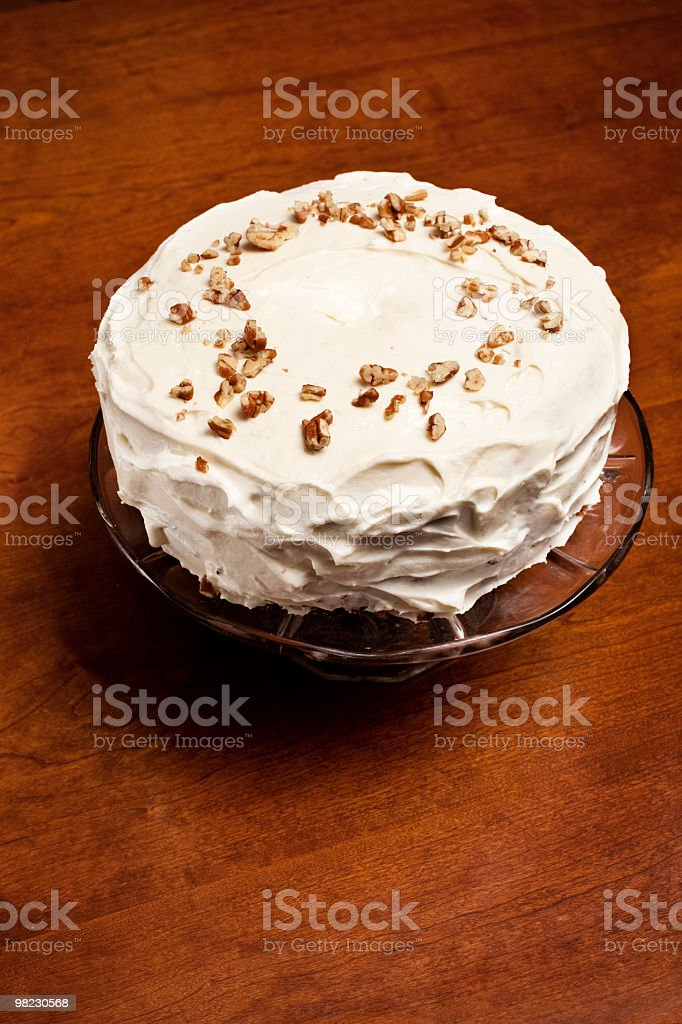 Pecan covered carrot cake on wooden table royalty-free stock photo