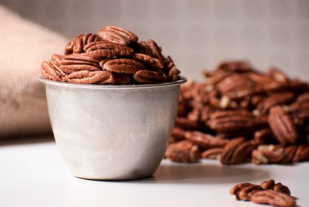 Pecan Halves Filling a Measuring Cup stock photo