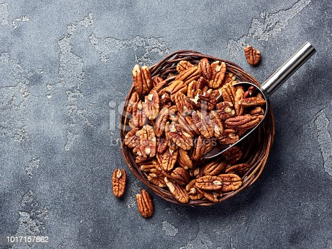 Pecan nuts and scoop on gray concrete background