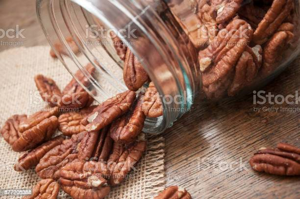 Pecan nuts falling from glass container on wooden table background picture id877208388?b=1&k=6&m=877208388&s=612x612&h=kp51flkiyjzai3onpm6vfkt4q7r2zp4rz1ewrhtncha=
