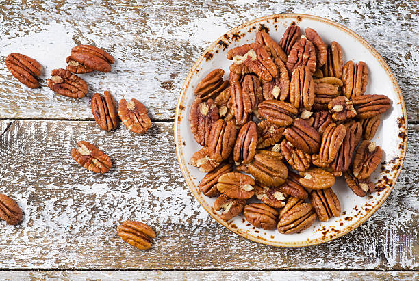 Pecan nuts on a wooden table. stock photo