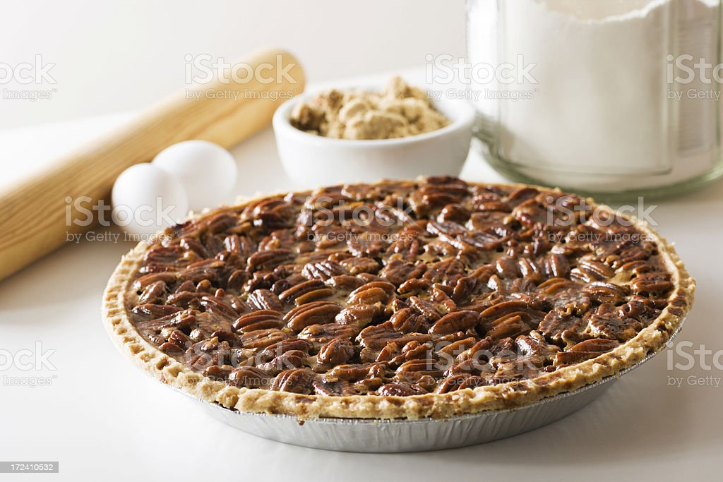 Pecan Pie, Fresh Baked Holiday Dessert with Ingredients, Rolling Pin A freshly baked pecan pie with ingredients and a rolling pin in the background. The delicious homemade dessert is ready for a holiday or other special occasion. Baked Stock Photo