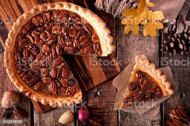 Pecan pie with slice removed table scene over wood picture id1042078220?b=1&k=6&m=1042078220&s=612x612&h=qlvouwdbk y2upmcpb 6c2pq994uivtn3drfurdzzog=