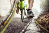 Detail of a green racing bicycle in motion on an old forest road.