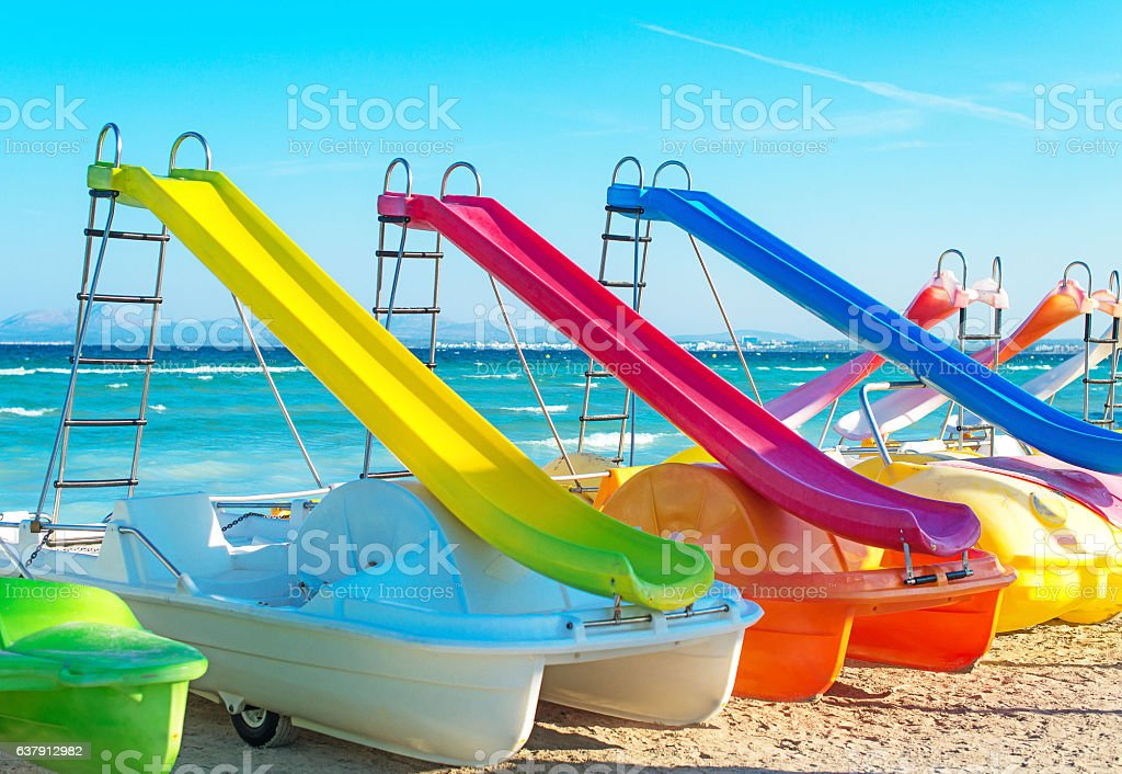 Pedal-boats with water slides on the beach. - foto de stock