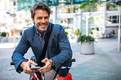 Smiling handsome businessman going to work with bicycle and holding mobile phone in hands on the street