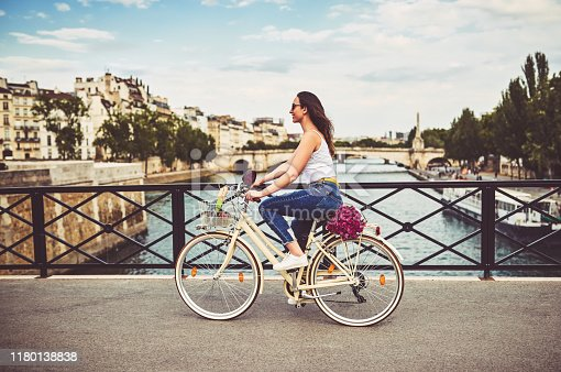 Shot of a young woman touring the city of Paris with a bicycle