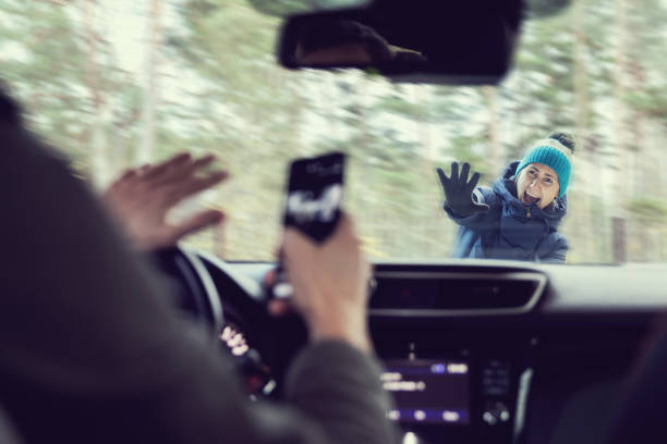 pedestrian accident - man using a phone while driving a car stock photo