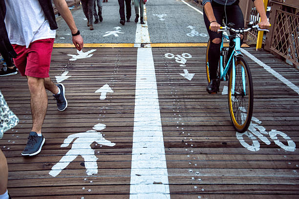 pedestrian and bicycle riders sharing the street lanes - fußgänger stock-fotos und bilder