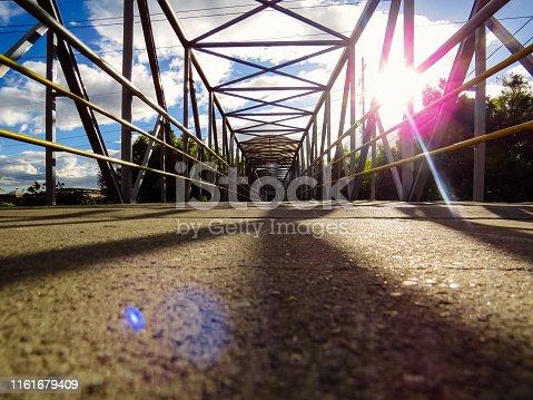 889637894 istock photo Pedestrian bridge in sunset with sunbeams 1161679409