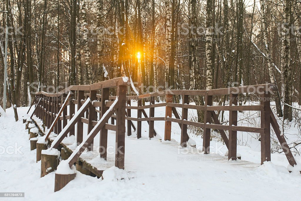 Pedestrian bridge on a snowy park at sunset stock photo