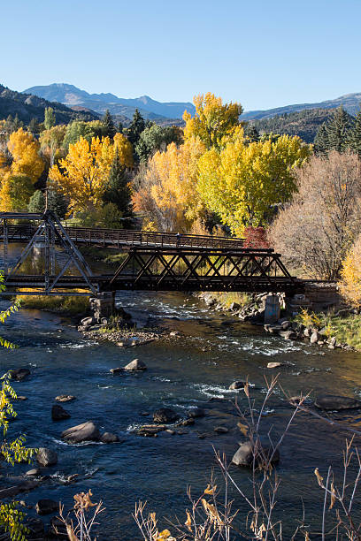 Pedestrian bridge over the Animas river in the autumn Pedestrian and railroad bridges are crossing the Animas river in the fall in Durango, Colorado.  In the distance, past the fall leaves are mountain peaks.  The freshwater of the Animas river is flowing through boulders and under the wooden and metal bridges. animas river stock pictures, royalty-free photos & images