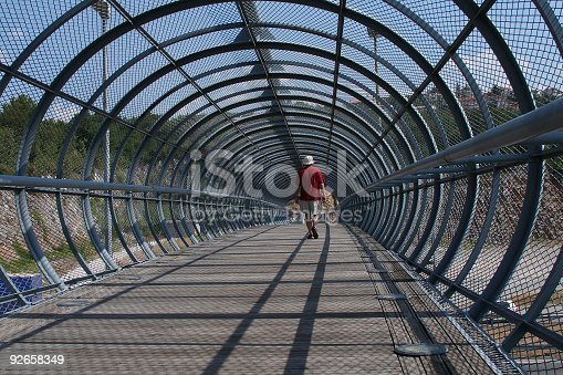 A pedestrian bridge , walkway,over the highway in Rijeka(Croatia), formed as a wooden bridge covered with a steel network. A men in red t-shirt crossing