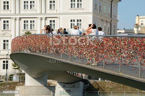 Salzburg, Austria - September 1, 2015: Pedestrian bridge with thousands of padlocks on barrier over Salzach river in Salzburg in Austria. Unidentified people visible.