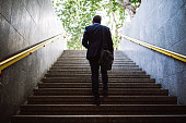 Pedestrian Businessman Walking Out Of Metro Up Stairs On Sunny Morning