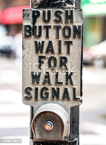 An old and weathered sign above a pedestrian crosswalk request button.