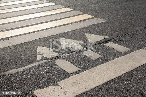 istock pedestrian crossing marking on asphalt - zebra and three arrows on a dark background 1165050785