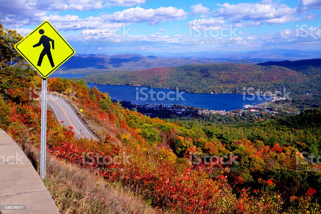 Pedestrian Crossing Sign at Top of Autumn Mountain with Lake stock photo