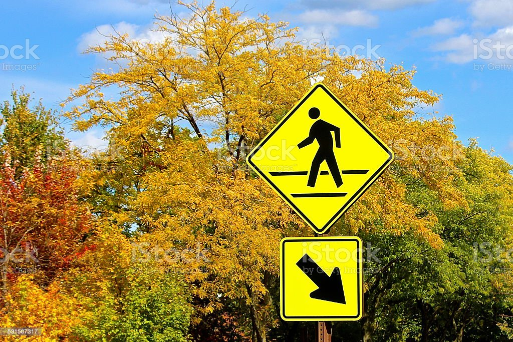 Pedestrian crossing sign with fall colors background stock photo
