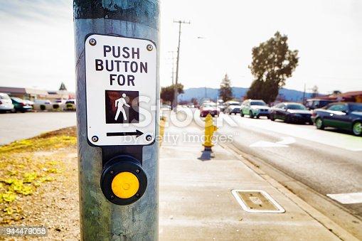 Pedestrian crosswalk button next to busy street in San Jose California.