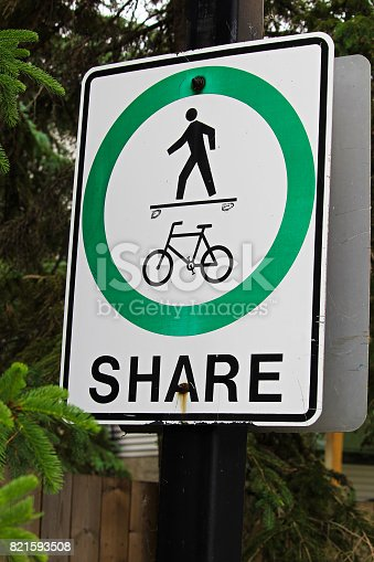 A pedestrian cyclist share path sign that has been vandalized to show a skateboarder instead.
