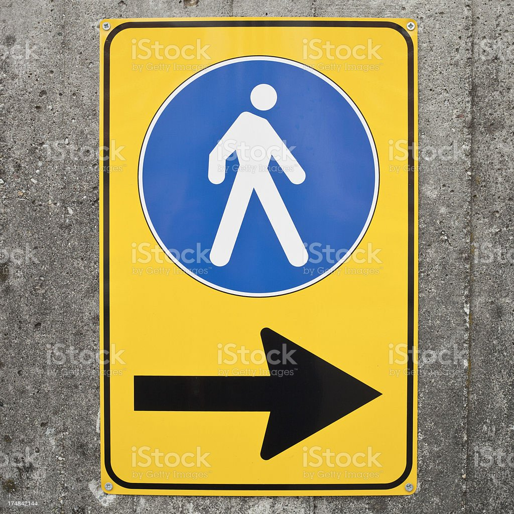 Pedestrian Direction Sign On Concrete Wall stock photo