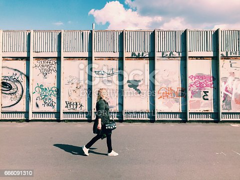 istock Pedestrian goes Graffiti wall background 666091310