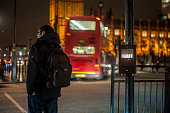 A pedestrian is waiting to cross the road, London. London is the capital and largest city of both the United Kingdom and England. Standing on the River Thames in southeastern England.