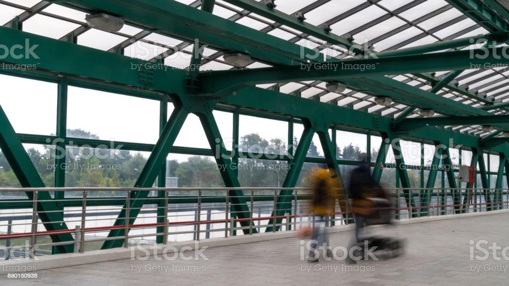 Pedestrian Motion Along Transparent Bridge Stock Photo