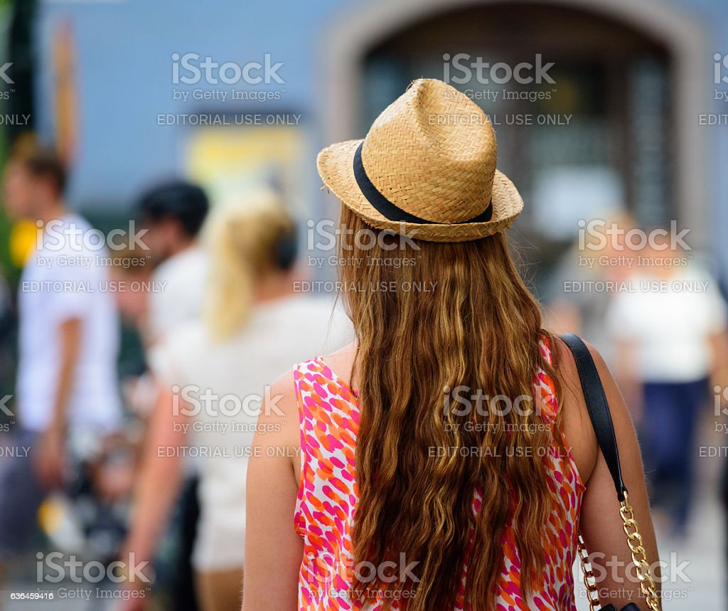 Pedestrian on sidewalk, wearing hat stock photo