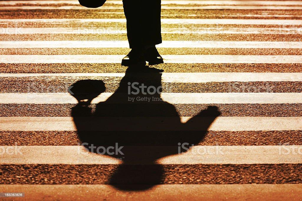 Pedestrian on zebra crossing in silhouette royalty-free stock photo