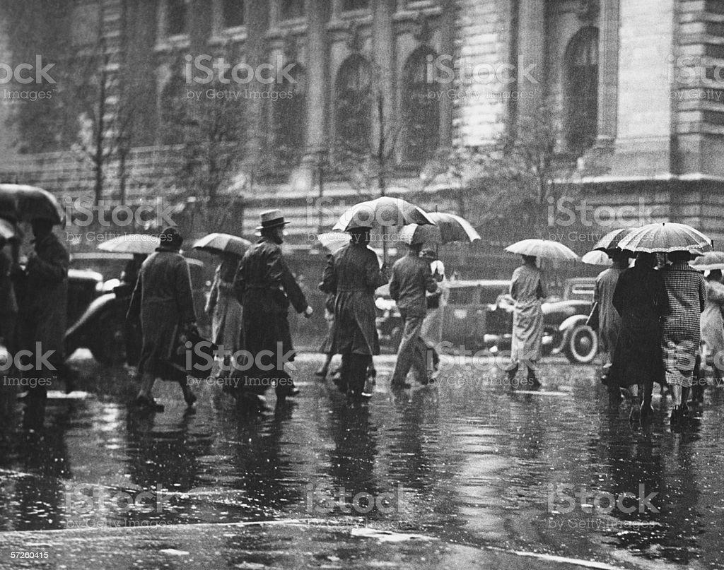 Pedestrian passing street, rainy weather, New York, USA (B&W) stock photo
