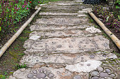 A pedestrian path made of stones and cement of bear feet shape for walking the garden. The walkaway is a ladder made of cement. In the park area. Natural background and peacefulness concept.