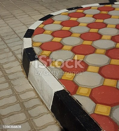 terracotta and grey designed path with newly painted edging blocks in repeating black and white