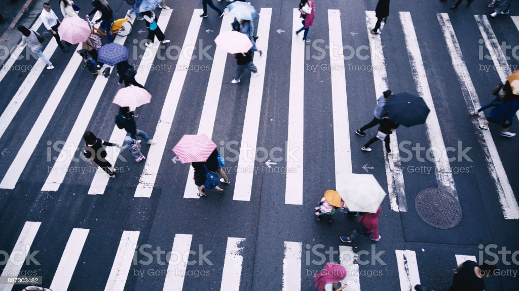 Pedestrian people cross a road in rainy day
