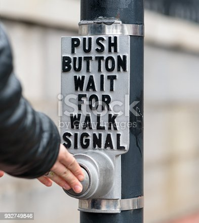 A woman pushing a traffic light pedetrian button to request a change in the lights.