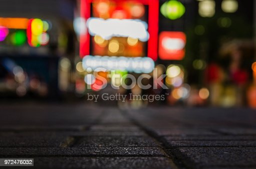 pedestrian road in the night city with a bright bokeh on the background. Blurry background texture of street at night in urban city environment.