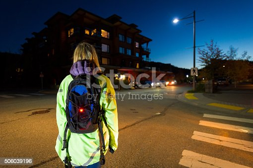 Pedestrian wearing a reflective jacket and wearing a safety light crossing the road at night