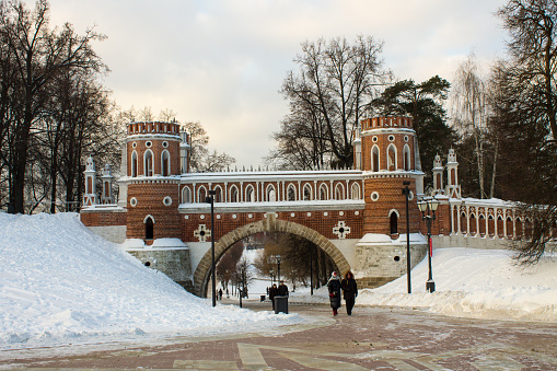 view of the red brick pedestrian shaped bridge in Tsaritsyno Park among bare trees on a winter day and a space for copying against a background of white snow in Moscow
